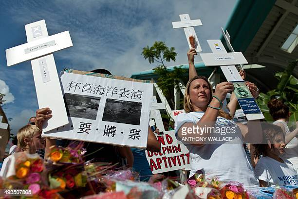 Protesters claiming there is no conservation in captive dolphin hold cross shaped placards outside local theme park Ocean Park during an 'Empty The...