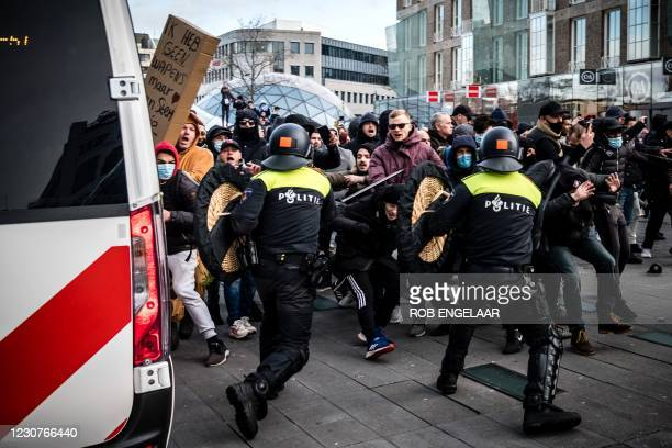 Protesters clash against Dutch anti-riot police officers during a demonstration against coronavirus restrictions on 18 Septemberplein square in...
