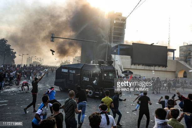 Protesters clash with an Iraqi riot police vehicle during a demonstration against state corruption and poor services between the capital Baghdad's...