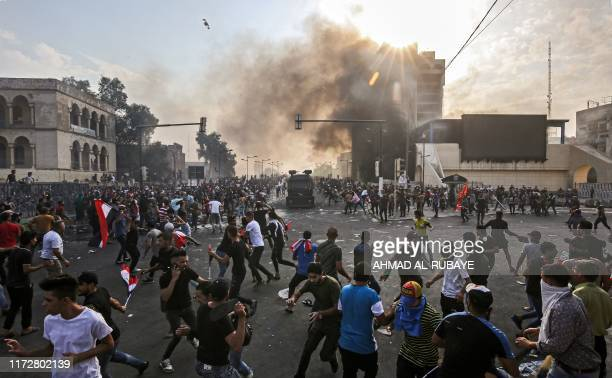 TOPSHOT Protesters clash with an Iraqi riot police vehicle during a demonstration against state corruption and poor services between the capital...