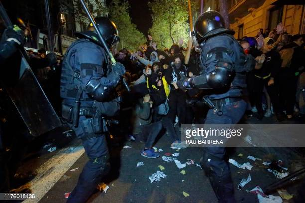 Protesters clash with Catalan regional police 'Mossos D'Esquadra' officers during a protest in front of the Spanish Government delegations in...