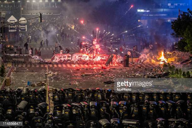 Protesters clash with Indonesian riot police during a demonstration in front of the Elections Supervisory Agency after the official government...