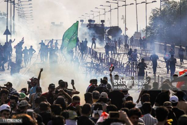 TOPSHOT Protesters clash with Iraqi riot police vehicles during a demonstration against state corruption and poor services between the capital...