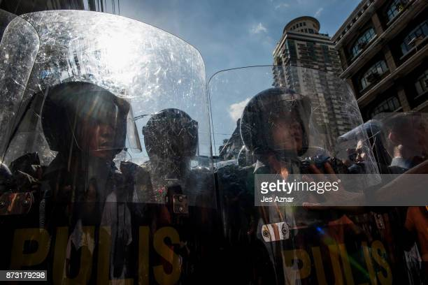 Protesters clash with police as they march in the streets of Manila on the day of US President Trump's arrival on November 12 2017 in Manila...