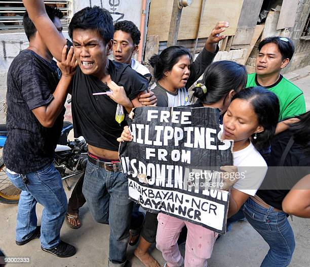 Protesters clash with police as US Secretary of State Hillary Clinton visits the typhoon affected Malanday High School in Marikina suburban Manila on...