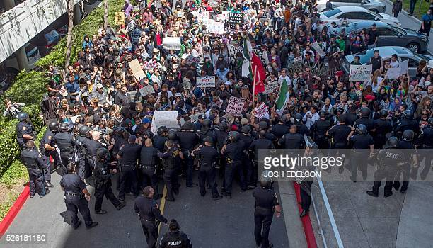 Protesters clash with police during a rally outside the Hyatt Regency Hotel where US Republican presidential candidate Donald Trump was speaking in...