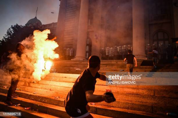 Protesters clash with police in front of Serbia's National Assembly building in Belgrade on July 8, 2020 during a demonstration against a weekend...