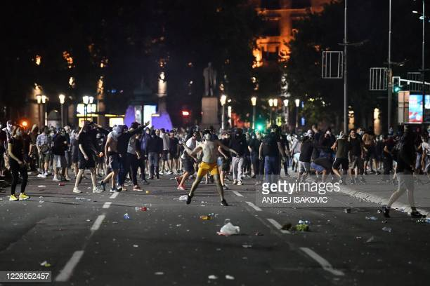 Protesters clash with police near the National Assembly building in Belgrade on July 10 during a demonstration against a weekend curfew announced to...