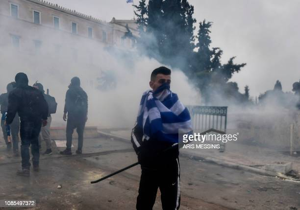 Protesters clash with riot police amid tear gas during a demonstration against the agreement with Skopje to rename neighbouring country Macedonia as...