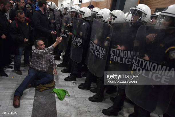 Protesters clash with riot police as they attempt to enter a courtroom in Athens on November 29 2017 People protesting homes' auctions clashed with...