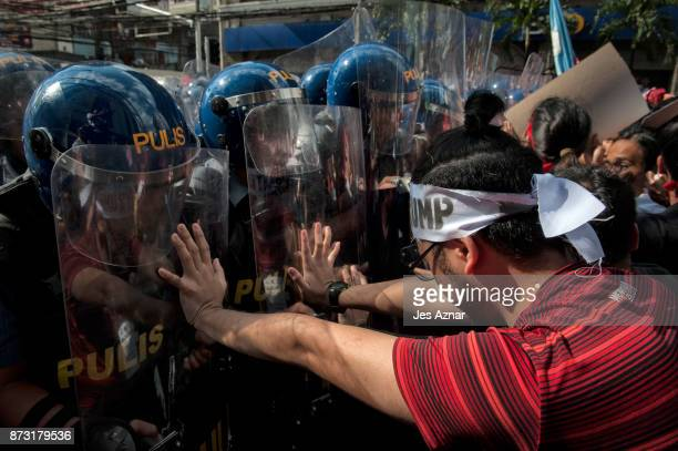 Protesters clash with riot police as they march in the streets of Manila on the day of US President Trump's arrival on November 12 2017 in Manila...