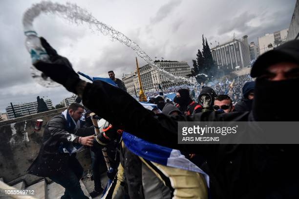 Protesters clash with riot police in front of the Greek Parliament in Athens on January 20 2019 during a demonstration against the agreement with...