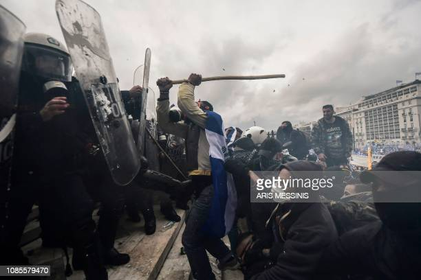TOPSHOT Protesters clash with riot police in front of the Greek Parliament in Athens on January 20 2019 during a demonstration against the agreement...