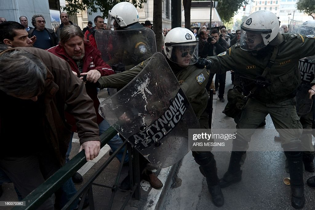 Protesters clash with riot police outside the Labour Ministry in Athens on January 30, 2013