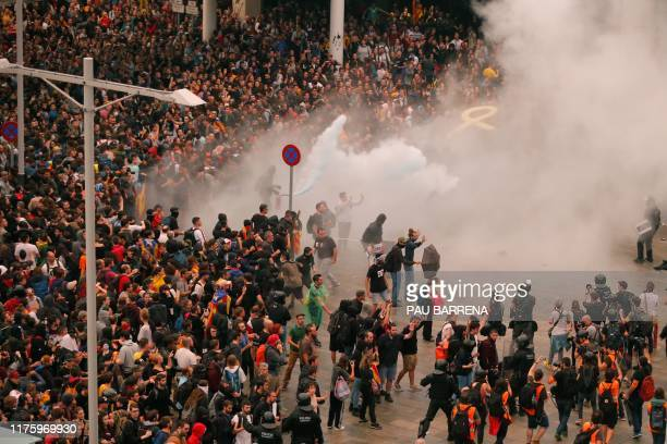 Protesters clash with Spanish policemen outside El Prat airport in Barcelona on October 14, 2019 as thousands of angry protesters took to the streets...