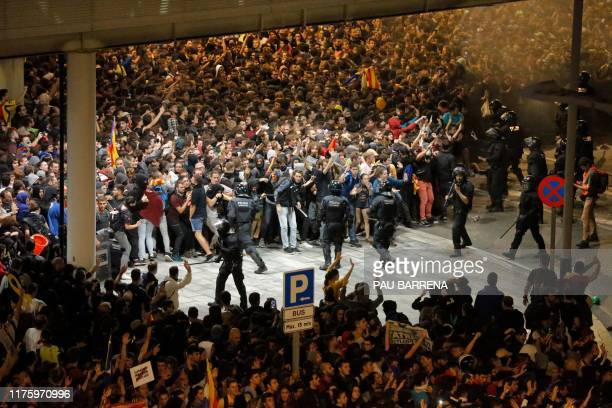 TOPSHOT Protesters clash with Spanish policemen outside El Prat airport in Barcelona on October 14 2019 as thousands of angry protesters took to the...