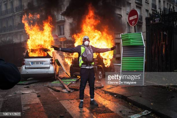 Protesters clashes with riot police on Foch avenue next to the Place de l'Etoile setting cars ablaze during a Yellow Vest protest on December 1 2018...