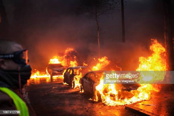 Protesters clashes with riot police on Kleber avenue next to the Place de l'Etoile setting cars ablaze during a Yellow Vest protest on December 1...