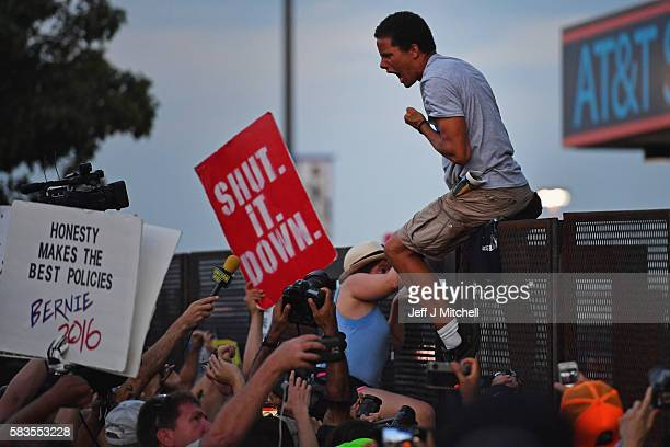 Protesters climb a fence near Wells Fargo Center on the second day of the Democratic National Convention on July 26 2016 in Philadelphia Pennsylvania...