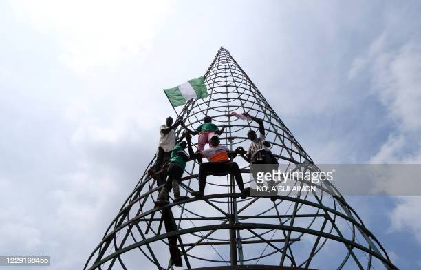 Protesters climb a telecommunication mast while carrying the Nigerian national flag during a demonstration to press for the scrapping of Special...