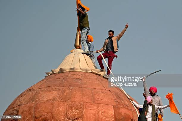 Protesters climb on a dome at the ramparts of the Red Fort as farmers continue to demonstrate against the central government's recent agricultural...