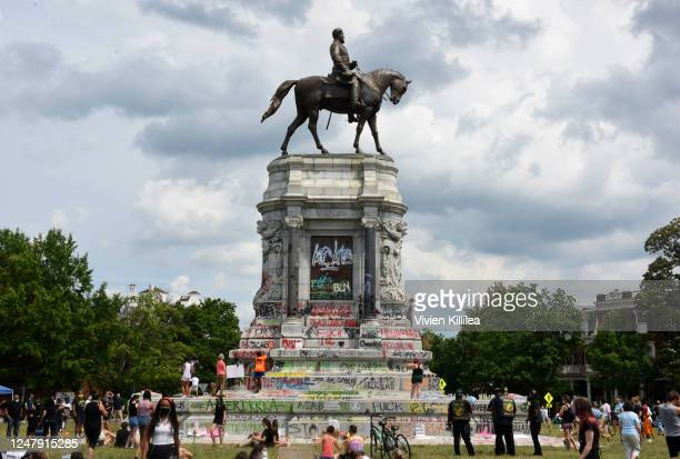 Protesters climb on the base of the statue of Confederate General Robert E Lee on Monument Avenue on June 6 2020 in Richmond Virginia amid continued...