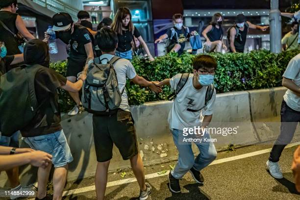 Protesters climb over a barrier during a clash after a rally against the extradition law proposal at the Central Government Complex on June 10 2019...