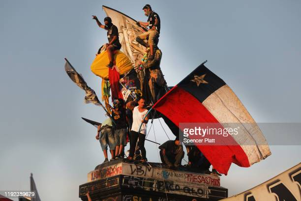 Protesters climb the General Baquedano's Monument a demonstration against Chilean President Sebastian Piñera the 50th consecutive day of unrest on...