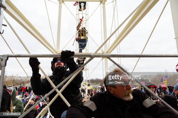 Protesters climb the scaffolding on the inauguration platform after breaking through barriers onto the grounds of the Capitol Building on January 6,...