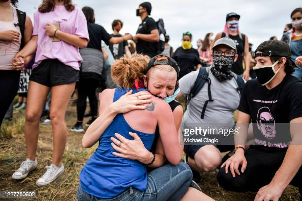 Protesters comfort a woman on the side of the highway after a car sped through the crowd and a man was shot while marching on I225 to protesting the...