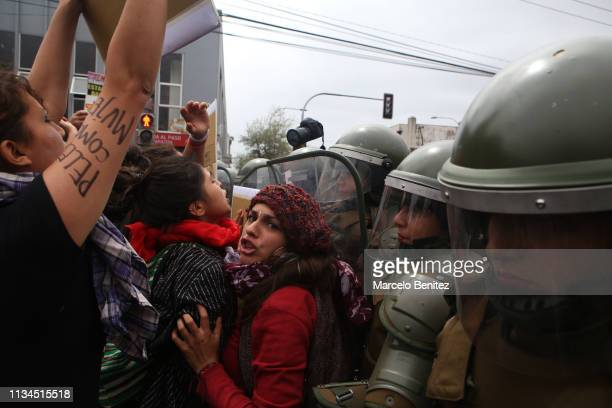 Protesters confront a line of riot police during a demonstration as part of the International Women's Day on March 8 2019 in Santiago Chile