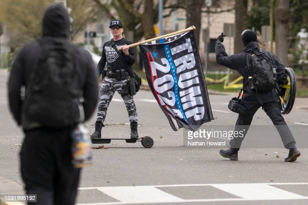 Protesters confront a Trump supporter on March 28, 2021 in Salem, Oregon. The protesters clashed with occupants of vehicles that had participated in...