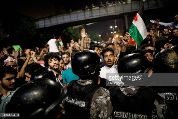 Protesters confront anti riot police during a demonstration against a draft income tax law near the prime minister's office in Amman Jordan on...