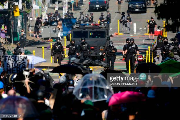 """Protesters confront police at the former location of the Capitol Hill Organized Protest after a """"Youth Day of Action and Solidarity with Portland""""..."""