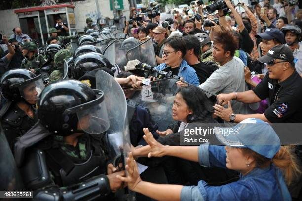 Protesters confront soldiers in riot gear blocking the route of an anti-coup march on May 24, 2014 in Bangkok, Thailand. Protesters defied a ban on...