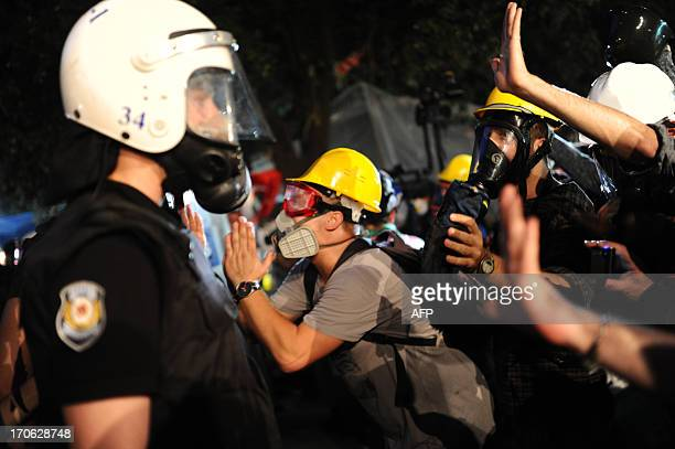 Protesters confront with the Turkish riot police before they move in Gezi Park in Istanbul on June 15 2013 Turkish police stormed an Istanbul park on...