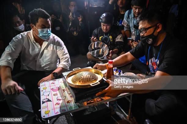 Protesters cook their dinner on a portable barbeque grill as the occupy the Ratchaprasong Intersection on November 18, 2020 in Bangkok, Thailand....