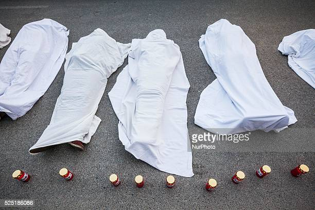 Protesters covered in a stage like bodies of immigrants that die trying to reach Europe during a demonstration in Warsaw against the Frontex European...