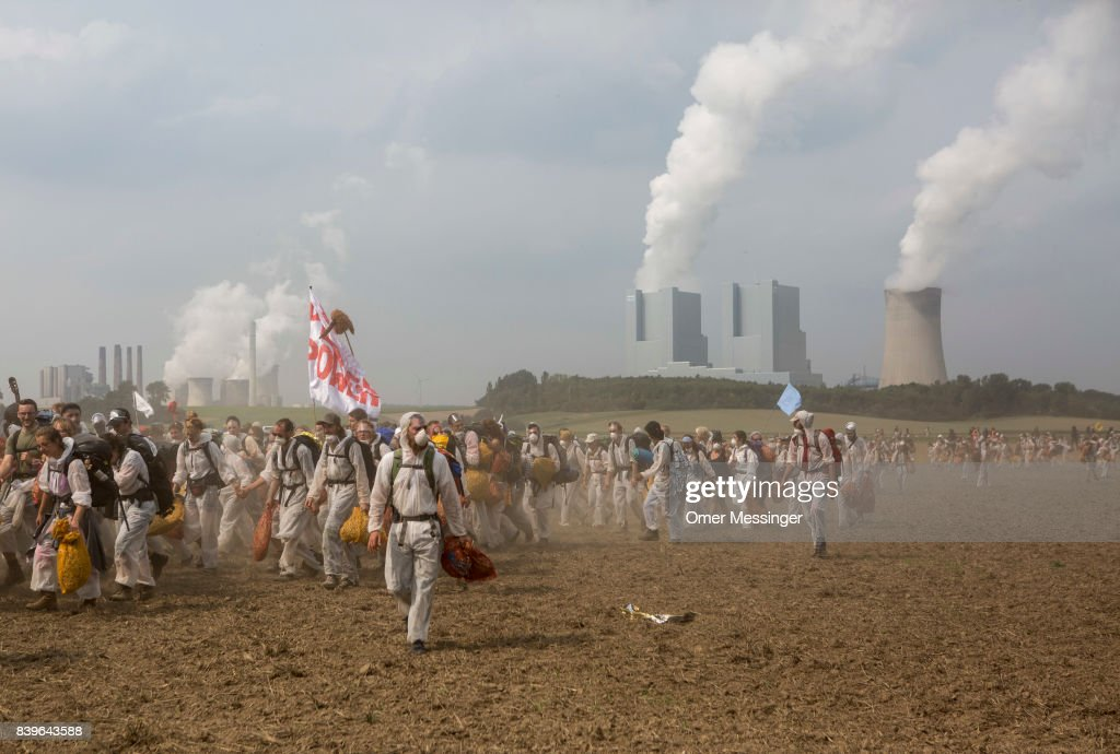 Protesters cross an open field to avoid German police in the Rhineland (Rhenisch) region of mines west of Cologne on August 26, 2017 near Rath, Germany. The group was on its way to block a rail track for trains transporting coal to the RWE Power AG power plant. Protesters seeking to bring attention to the impact of coal on climate change have converged on the region for two days of disruptive disobedience. The mines, which include the Hambach, Garzweiler, Inden and Bergheim mines, are operated by German utility RWE and produce lignite coal.