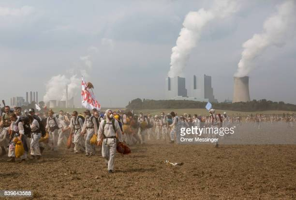 Protesters cross an open field to avoid German police in the Rhineland region of mines west of Cologne on August 26 2017 near Rath Germany The group...