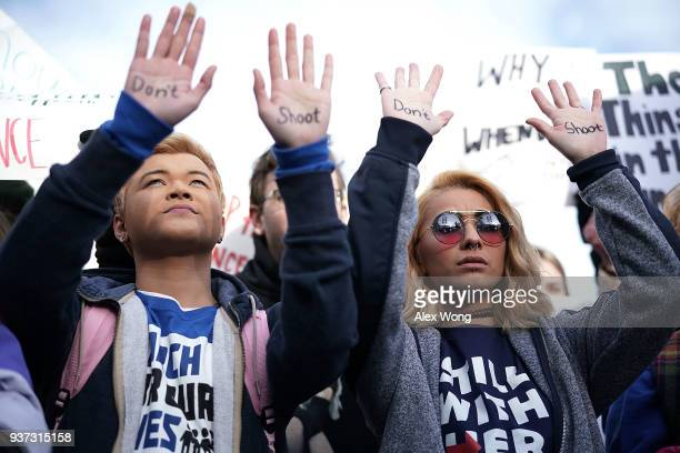 Protesters Daisy Hernandez of Virginia and Hunter Nguyen of Maryland hold their hands up as they wait for the beginning of the March for Our Lives...