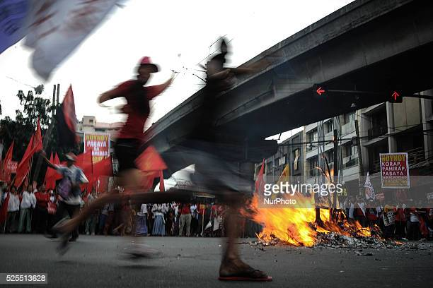 Protesters dance around a burning effigy depicting President Aquino during a demonstration outside the presidential palace in Manila Philippines...