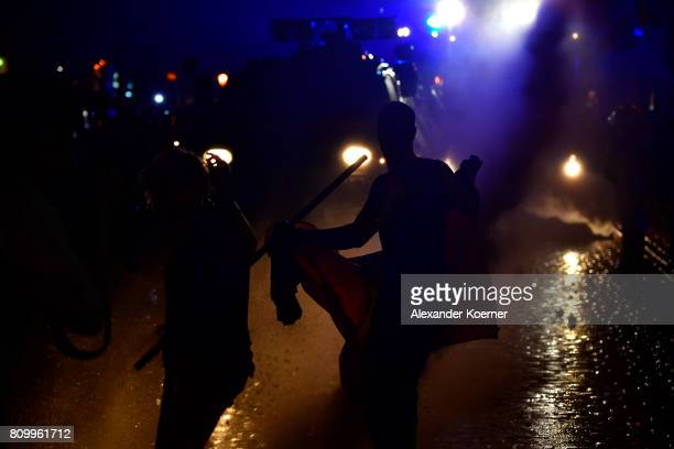 Protesters dance in front of a water-cannon after erecting burning barricades in front of the Rote Flora left-wing centre during a march on July 7,...