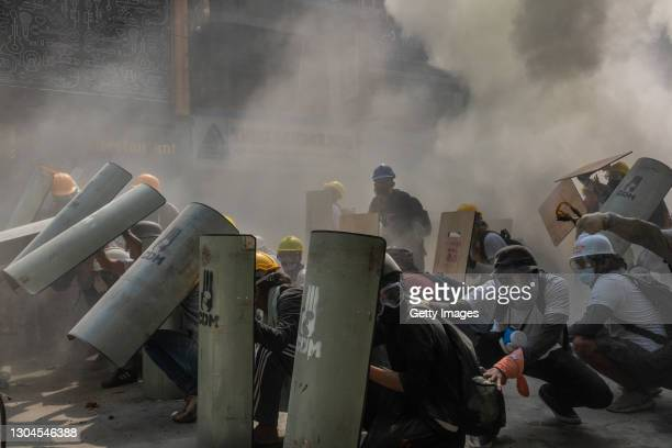 Protesters defend themselves with makeshift shields during clashes with riot police on February 28, 2021 in Yangon, Myanmar. Myanmar's military...