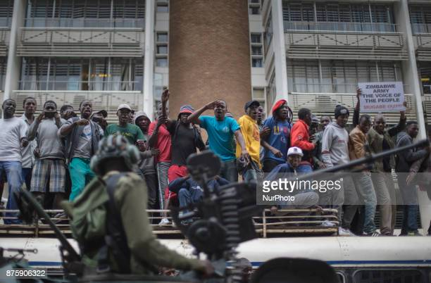 Protesters demanding President Robert Mugabe stand down look up and cheer as an army helicopter flies over the crowd as they gather in front of an...