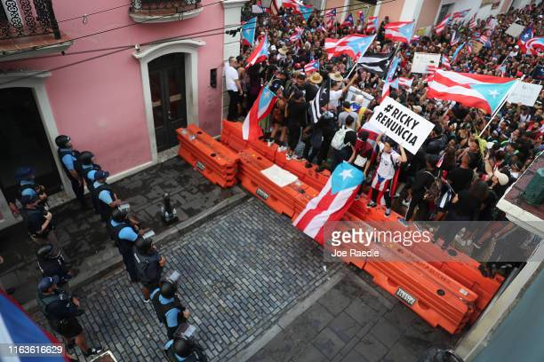 Protesters demonstrate against Ricardo Rossello the Governor of Puerto Rico near police that are manning a barricade set up along a street leading to...