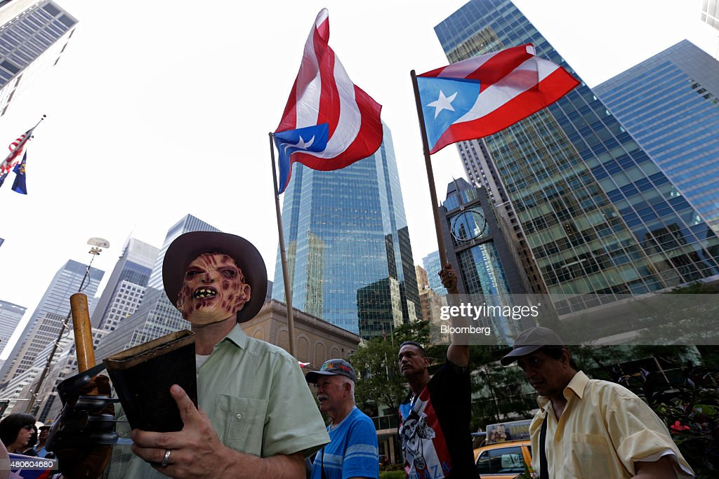 Protesters demonstrate at the Puerto Rican debt talks outside Citibank Inc. headquarters on Park Avenue in New York, U.S., on Monday, July 13, 2015. Puerto Ricos top finance official said its too soon to discuss how investors will be affected as it seeks to restructure $72 billion of debt that its struggling to pay because of the islands stagnant economy. Photographer: Peter Foley/Bloomberg via Getty Images