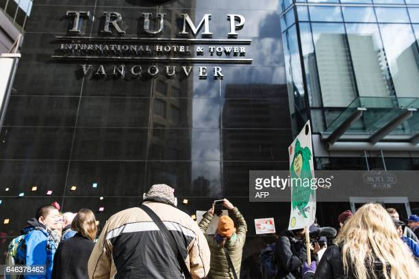 Protesters demonstrate by writing messages on the opening day for the Trump International Hotel and Tower in Vancouver on february 28 2017 / AFP /...