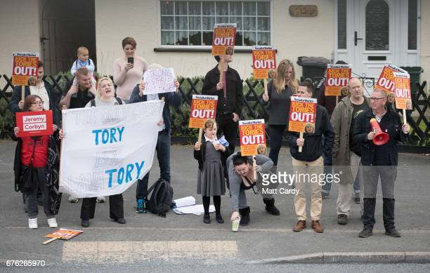 Protesters demonstrate outside as Britain's Prime Minister Theresa May addresses an audience of supporters during a campaign stop on May 2 2017 in...