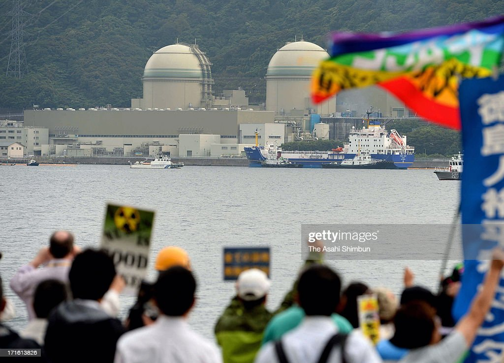 Protesters demonstrate while a container of mixed oxide (MOX) fuel is unloaded from a freighter at Kansai Electric Power Co Takahama Nuclear Power Plant on June 27, 2013 in Takahama, Fukui, Japan. Protesters oppose outside the plant as this is the first shipment of MOX fuel since the meltdowns at the Fukushima No. 1 power plant arrived in Japan, which plutonium stockpile is already equivalent to 5,000 Nagasaki-type atomic bombs.